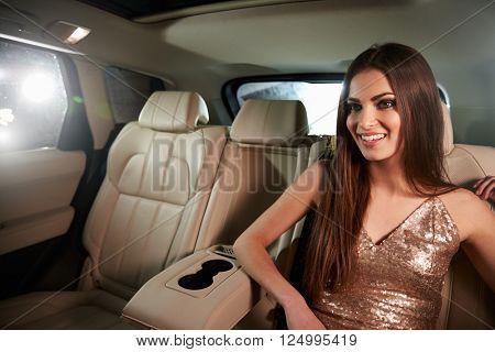 Glamorous dark haired young woman sitting in back of a limo