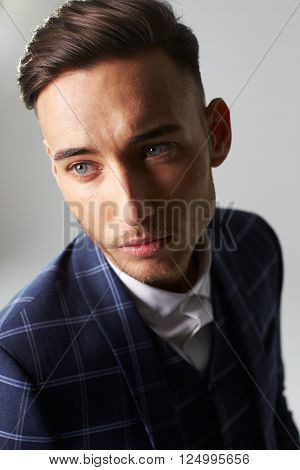 Close-up portrait of young man wearing a suit, looking away