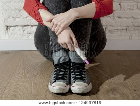 conceptual image hand of pregnant teenager girl or young desperate woman holding positive pink pregnancy test sitting on home floor in unwanted baby and unexpected motherhood concept poster