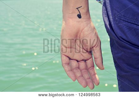 closeup of a young caucasian man seen from behind with a musical note painted in his wrist