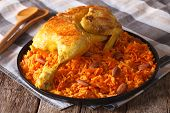 Arabic food: kabsa with chicken and almonds close-up on a plate. Horizontal poster