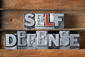 self defense phrase made from metallic letterpress type on wooden tray poster