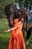 Longhaired girl in an orange gypsy dress interacts with a bay horse poster