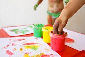Child dipping fingers in washable non-toxic finger paints painting a drawing. Sensory play creativity fun childhood concept. poster