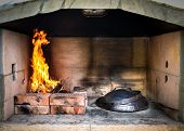 Cooking of traditional Balkan Greek Mediterranean Croatian meal Peka in metal pots called sac sach or sache or a metal lid. Fireplace with open fire and burning coals. poster