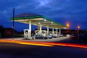 gas station at night with car light trails poster