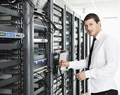 young handsome business man it engeneer in datacenter server room poster