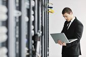 young it engineer business man with thin modern aluminium laptop in network server room poster