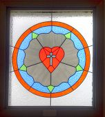 The shape of a heart in a stained glass inside a church. poster