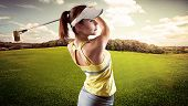 Energetic woman practicing golf exercise over beautiful landscape background. Pretty sportswoman hitting the ball with golf club. poster