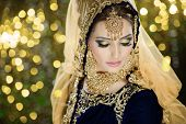 Portrait of a beautiful female model in traditional ethnic asian indian bridal costume with heavy makeup and jewellery poster