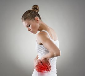 Young female touching her left side in pain. Kidney inflammation and therapy. Medicine and health care concept.