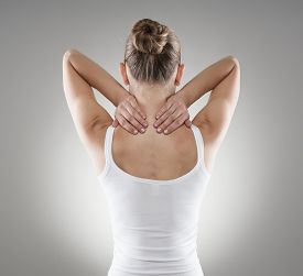 Portrait of young woman massaging her painful neck over grey background. Muscle spasm and backache concept.