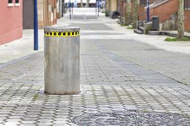 Closeup image of Automatic bollard with yellow color warning sign in a pedestrian street.