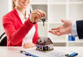 Closeup of smiling woman realtor giving key of new apartment to client. Female house agent sitting at the desk with house miniature and plan.