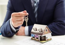 Male realtor selling house or apartment giving a key to client