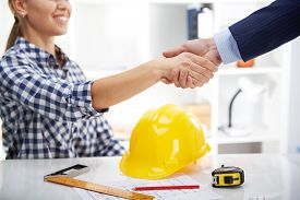 Happy smiling woman architect meeting customer at workplace. Project development concept.
