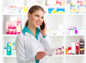 Portrait of female pharmacist consulting customer on phone holding recipe. Young woman medical assistant in pharmacy.