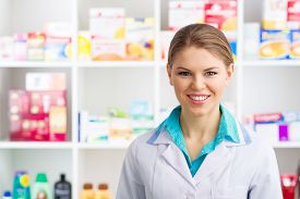 Young salesperson in drug store posing over medicines background. Happy smiling woman pharmacist in labcoat servicing customers.