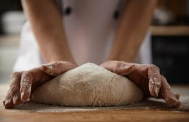 Close-up of female cook hands kneading dough for pizza or pasta in the kitchen. Healthy food preparation.