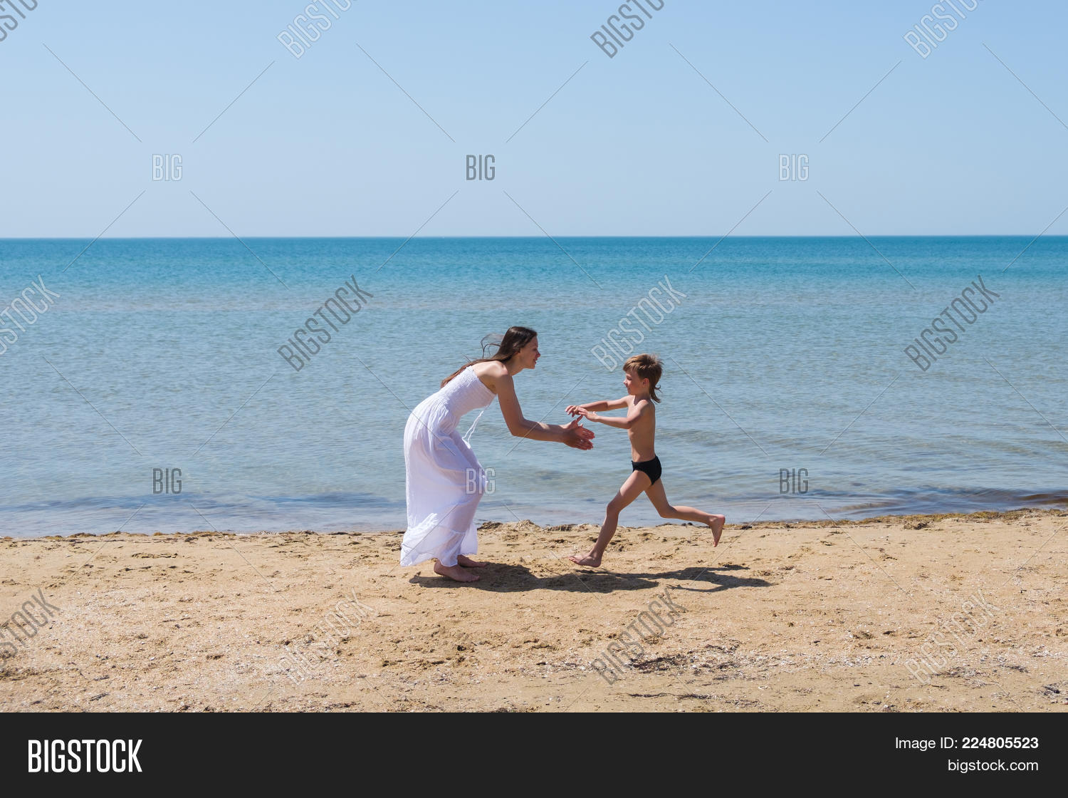 A Boy In A Black Speedo Running To Mom Brunette In A White Dress On The