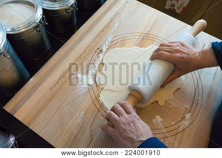 woman rolling pie crust on a wooden board with rolling pin