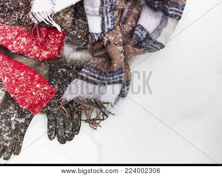 Bunch of winter garments and clothes laid under falling snow, above view