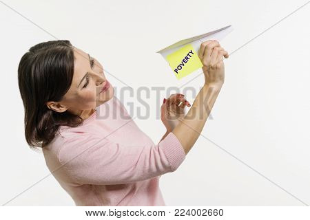 A woman gets rid of poverty. Sends to the sky an abstract plane signed by the word Poverty.
