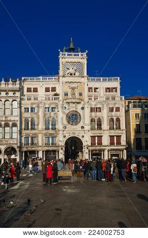 VENICE, ITALY - DECEMBER 24: Tourists in front of Saint Mark Clocktower with the famous Moors at the top December 24, 2017 in Venice, Italy