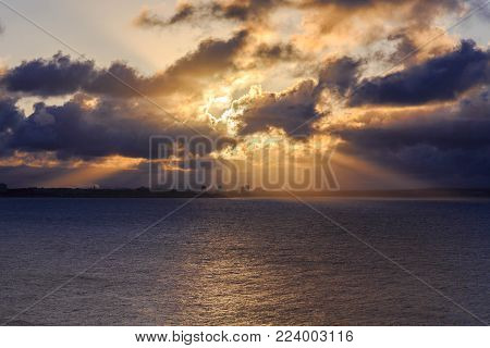 City on the horizon on the Atlantic coast in the breaking rays of the dawn sun through the clouds, Algarve, Portugal