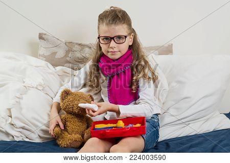 Sick child girl in glasses, heals his sick Teddy bear