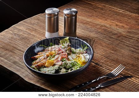 Caesar salad. Caesar dressing is sour taste of vinegar. Often served with Green Cos, topped with Parmesan cheese Costa biscuits, bacon and egg. I like to eat healthy food. Low calorie. Dark plate on wooden background