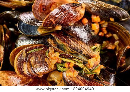 Closeup macro cooked mussels with chopped vegetables. Close up steamed mussels.