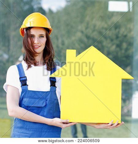 Forewoman presenting yellow house symbol, construction concept