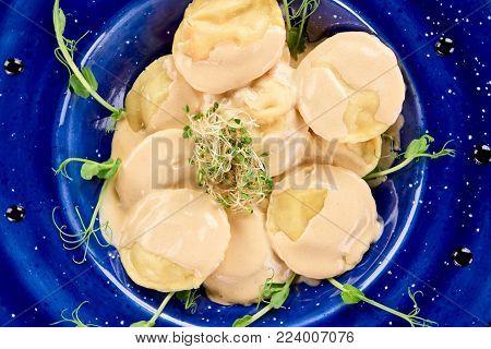 Dish with ravioli close up. Decorated ravioli on blue plate.