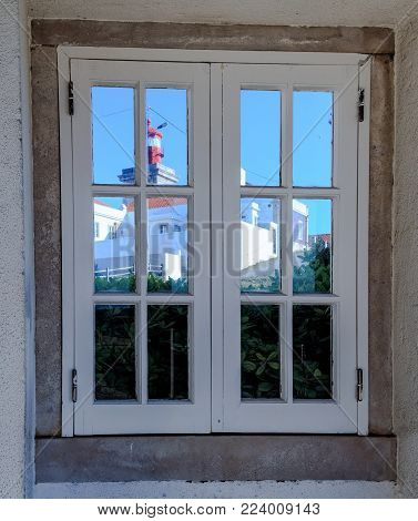 A reflection of the lighthouse in Cabo da Roca in the window, Portugal, the westernmost cape of the continent