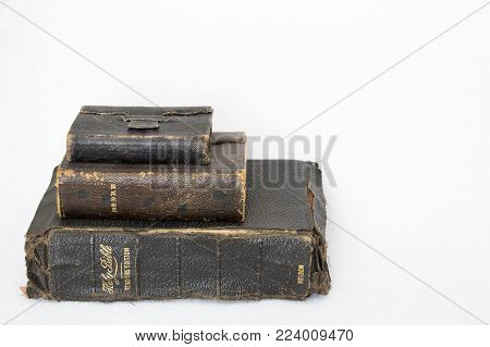 Stack of Three Worn Antique Leather Bibles on White Background