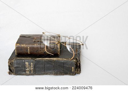 Two Antique Leather Bibles with Antique Eye Glasses on White Background