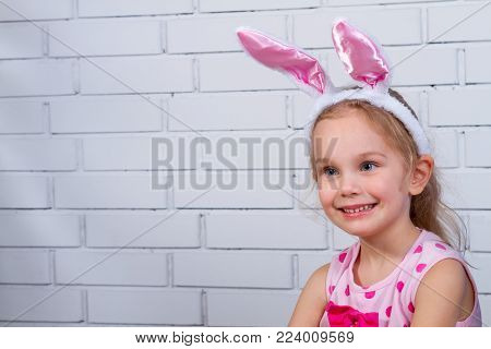 Happy little girl with pink rabbit ears. Portrait of cute caucasian baby wearing bunny ears. Easter holidays concepts.