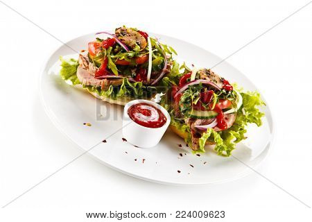 Sandwiches with meat and vegetables on white background