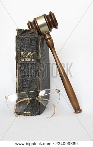 Antique Worn Leather Bible with Antique Rimless Eye Glasses and Wooden Gavel on White Background