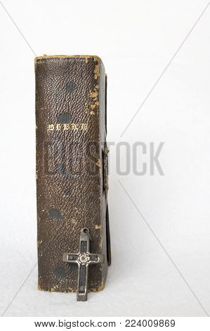 Single Antique Brown Bible with Small Antique Cross on White Background