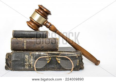 Antique Worn Leather Bibles with Antique Rimless Eye Glasses and Wooden Gavel on White Background