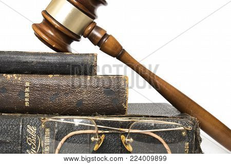 Three Antique Leather Bibles Stacked with Glasses and Gavel Against White Background
