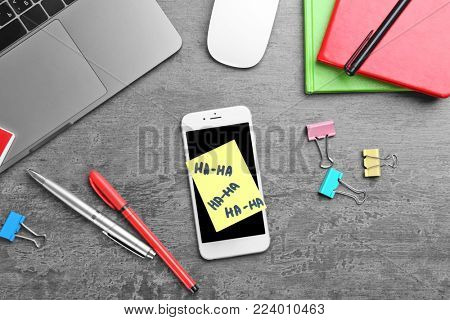 Smartphone and sticky note on office table. April fool's day celebration