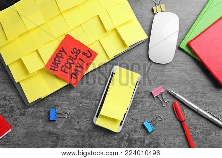 Smartphone and laptop covered in sticky notes. April fool's day celebration