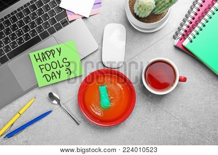 Plate with jelly and stapler on office table. April fool's day celebration
