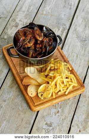Top view saucepan with mussels and side dish. Dish with mussels on wooden board, top down view.