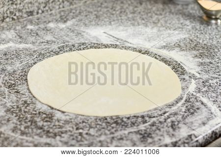Pizza dough on table. First step of cooking pizza.