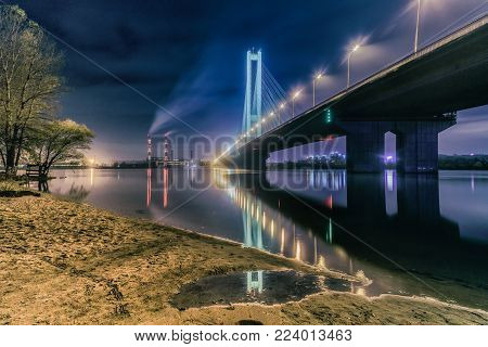 Bridge at sunset across the Dnieper River. Kiev bridge against the backdrop of a beautiful sunset in Kiev. Bridge in evening sunshine.